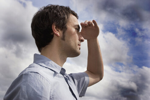 Young man against cloudy sky, shielding eyes, side view, close-up - CLF00235