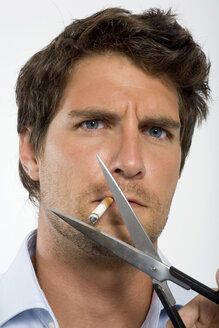 Young man cutting cigarette with scissors, close-up, portrait - WESTF01630