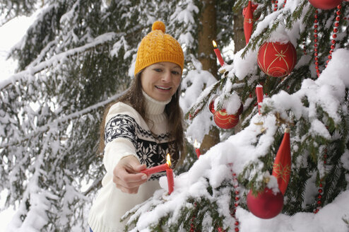 Young woman decorating Christmas tree in snow, smiling - HHF00536