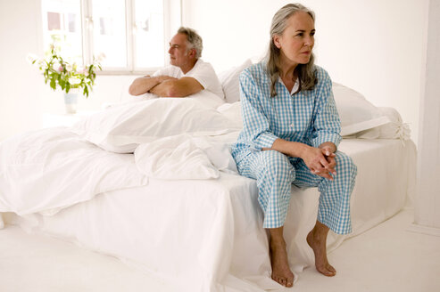 Mature couple sitting on bed (focus on woman in foreground) - WESTF01966