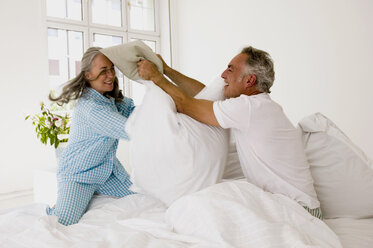 Mature couple having pillow fight on bed - WESTF01930