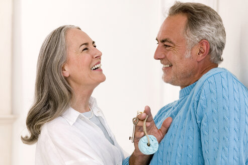 Mature couple smiling, man holding key, close-up - WESTF01894