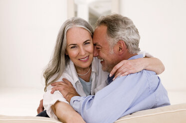 Mature couple embracing on sofa, smiling - WESTF01888