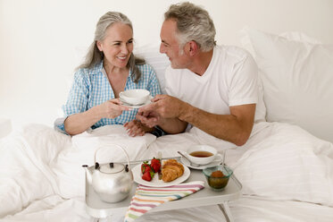 Mature couple sitting on bed with breakfast, smiling - WESTF01876