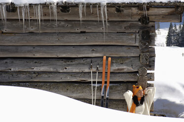 Woman sitting in front of alpine hut - HHF00713