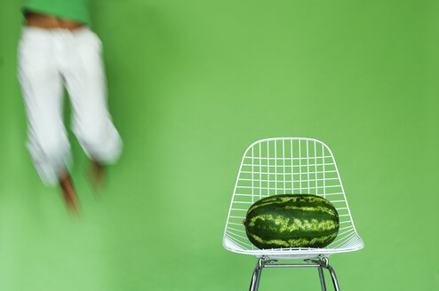 Young woman jumping by watermelon on chair, (blurred motion) - ASF02417