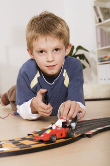 Boy (6-7) playing with toy cars, portrait - RDF00140