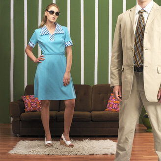 Young woman and man standing in living room - JL00178
