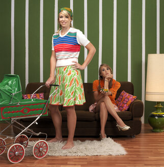 Young woman with baby stroller standing by woman sitting on sofa - JL00172