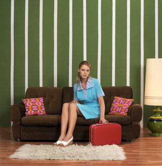 Woman with suitcase sitting on sofa - JL00169