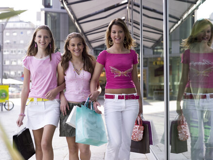 Teenage girls with shopping bags, smiling, portrait - KMF00383