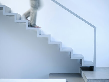 Man moving down stairs, side view - KM00491