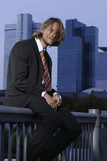 Young business man sitting on railing - KM00458