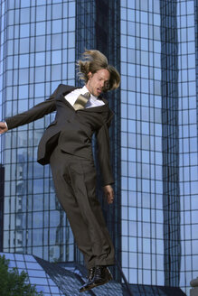 Young businessman jumping in front of Deutsche Bank Tower - KM00449