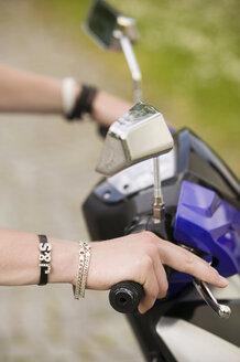 Man holding handle bar of moped, close-up - KMF00237