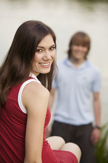 Young woman smiling with young man in background - KMF00231