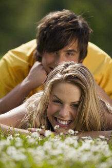Young couple lying in meadow, smiling - KMF00216