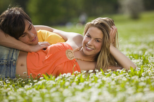 Young couple lying in meadow, smiling - KMF00213