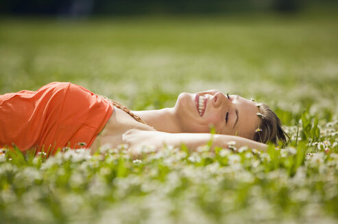 Teenage girl lying in meadow - KMF00210