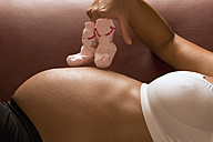 Pregnant woman holding pair of baby shoes - LDF00288
