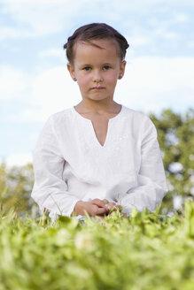 Girl (7-9) sitting in meadow - LDF00354