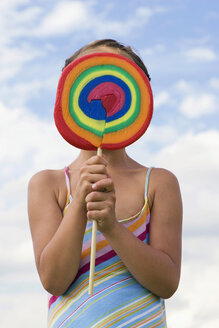 Girl (7-9) holding lollipop in front of face - LDF00330