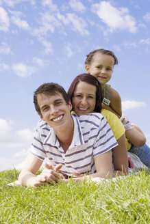 Parents with daughter (7-9) lying on grass, portrait, close-up - LDF00327