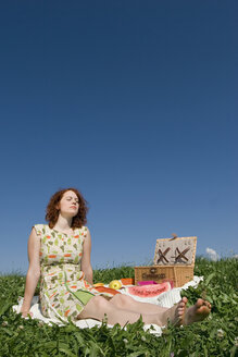 Young woman sitting on picnic blanket, eyes closed - LDF00213