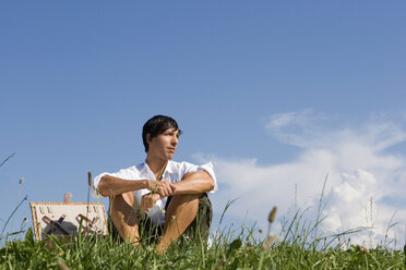 Young man sitting in meadow - LDF00210