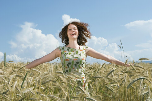 Young woman standing in cornfield, arms out, smiling - LDF00201