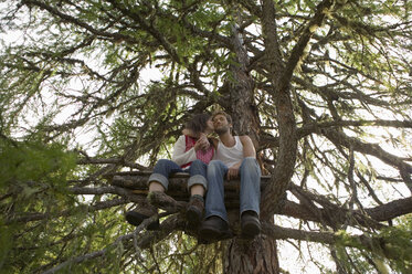 Young couple sitting on tree house, kissing - BABF00223