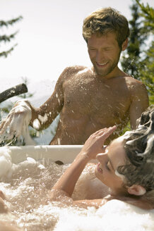 Young couple, woman in tub splashing water - BABF00157