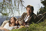 Young couple lying in meadow, having picnic - BABF00070