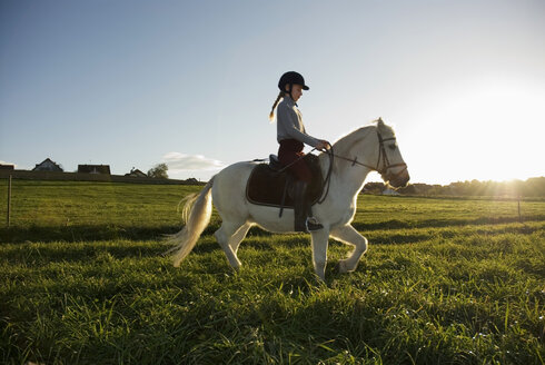 Girl (7-9) riding pony, side view - WESTF02942