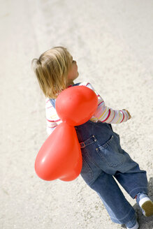 Girl ( 3-4 ) holding bunch of balloons, rear view - SMOF00091