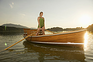 Young woman standing on rowing boat in lake - ABF00109