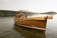 Young woman sitting on rowing boat in lake - ABF00106