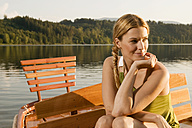 Young woman sitting on rowing boat in lake - ABF00103