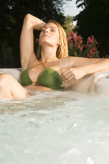 Woman relaxing in bathtub, holding drink - ABF00097