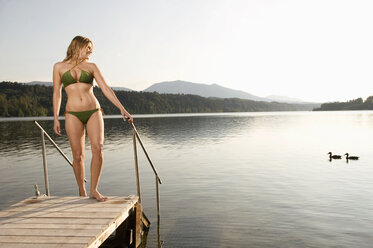 Woman standing on jetty - ABF00094