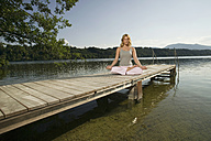 Woman exercising yoga on jetty - ABF00076