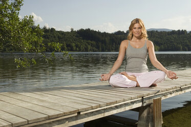 Woman exercising yoga on jetty - ABF00073