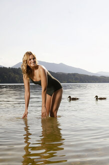 Woman bending in lake, smiling - ABF00067