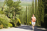 Italy, Tuscany, man jogging on street - MRF00773