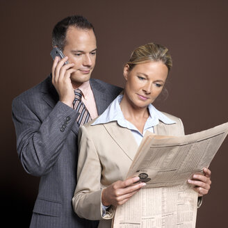 Businessman and businesswoman man using mobile phone, woman holding newspaper - JLF00221