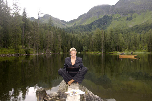 Businesswoman sitting at lake with laptop - HHF00825