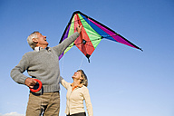 Senior couple, man holding kite - WESTF03521