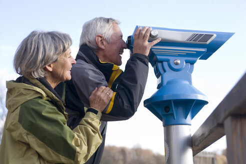 Senior couple, man looking through telescope, side view - WESTF03500