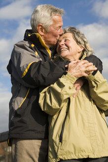 Senior couple, man kissing woman, smiling - WESTF03491