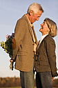 Senior couple, man hiding bouquet, side view - WESTF03479